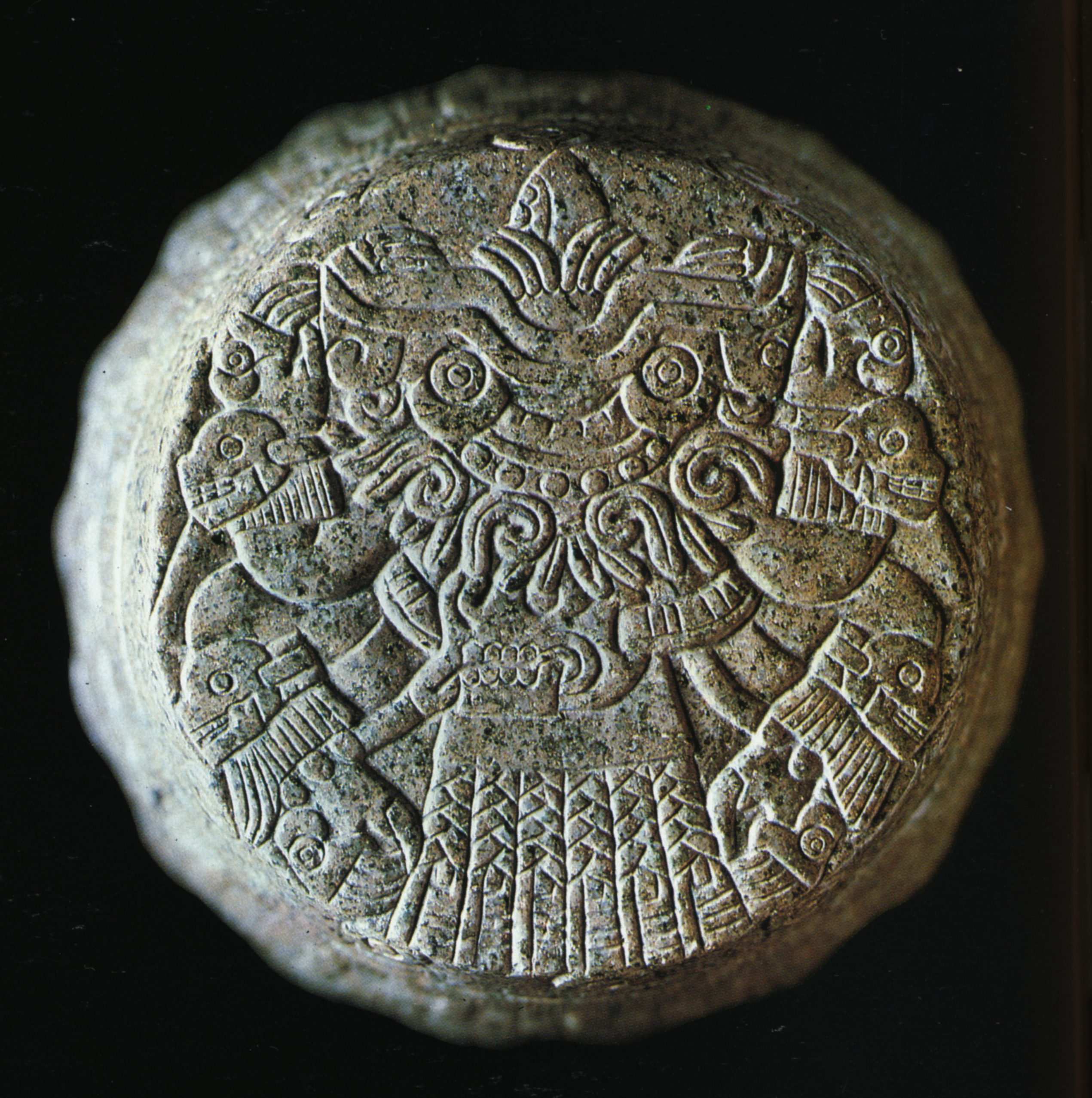 FIGURE 1. Image of Tlaltecuhtli on the base of a greenstone cuauhxicalli  (large stone bowl) in the Ethnologisches Museum, Berlin. The goddess faces upwards, with a flint knife emerging from her open mouth. Her clawed hands and feet have eyes, and she wears human skulls around her wrists and knees.
